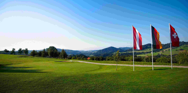 Golfplatz des Golfclubs Oberstaufen-Steibis mit grüner Wiese, Bergpanorama und drei Länderflaggen von Österreich, Deutschland und der Schweiz