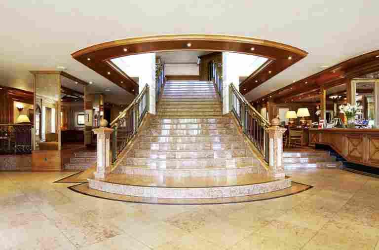 Foyer der Allgäu Sonne mit Rezeptionsbereich und großer Treppe