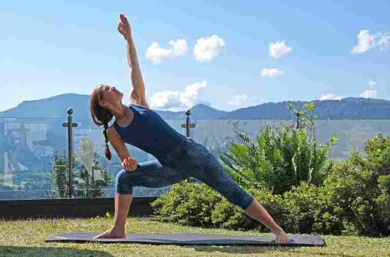 Yogalehrerin Melanie bei einem Yogakurs an der frischen Luft vor schönem Bergpanorama