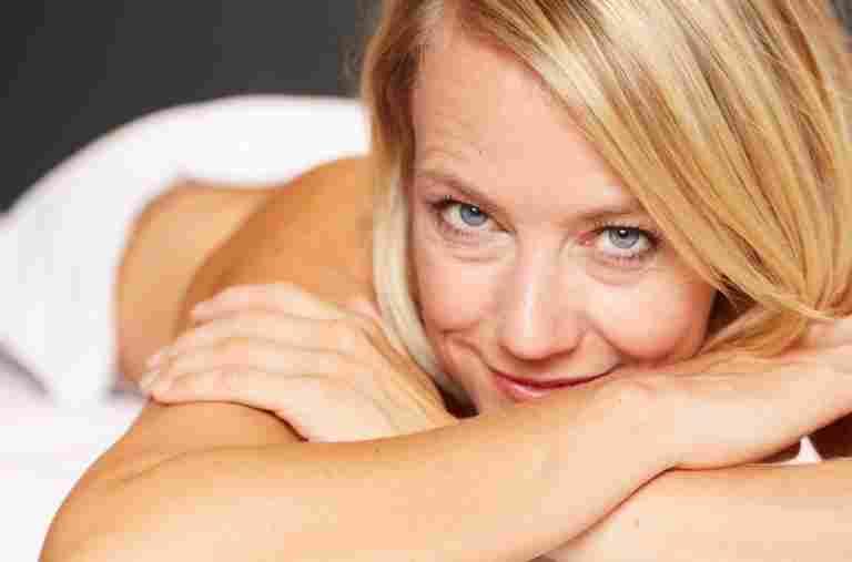 Glückliche Frau auf einer Massageliege