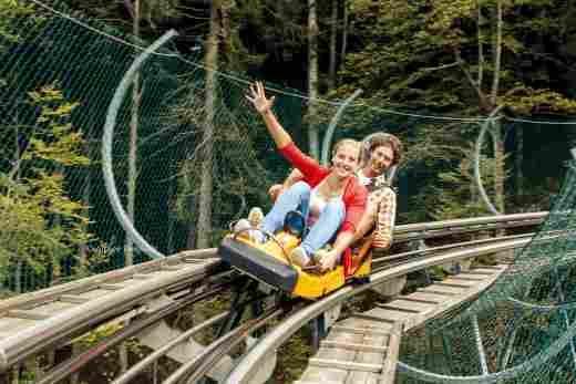 Glücklich lächelndes, junges Pärchen, das mit dem Alpsee Coaster fährt