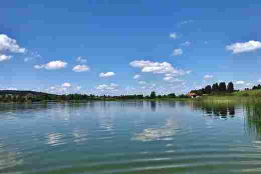 Blick auf den Niedersonthofener See im Sommer mit grüner Landschaft