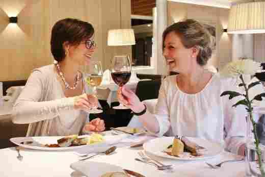 Zwei Freundinnen sitzen im Restaurant am gedeckten Tisch und stoßen mit ihren Weingläser an