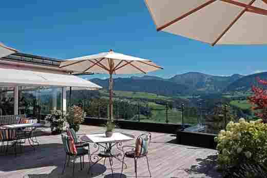 Die Sonnenterrasse neben unserer Fitnesswelt mit Sonnenschirmen, Gartentischen und -stühlen sowie schönem Bergblick