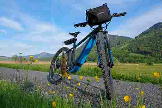 Blaues E-Mountainbike auf einem Schotterweg mit einer grünen Landschaft