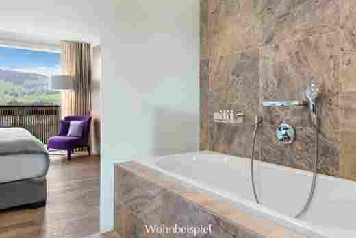 Badewanne in der Juniorsuite mit Blick ins Schlafzimmer und auf die Berge